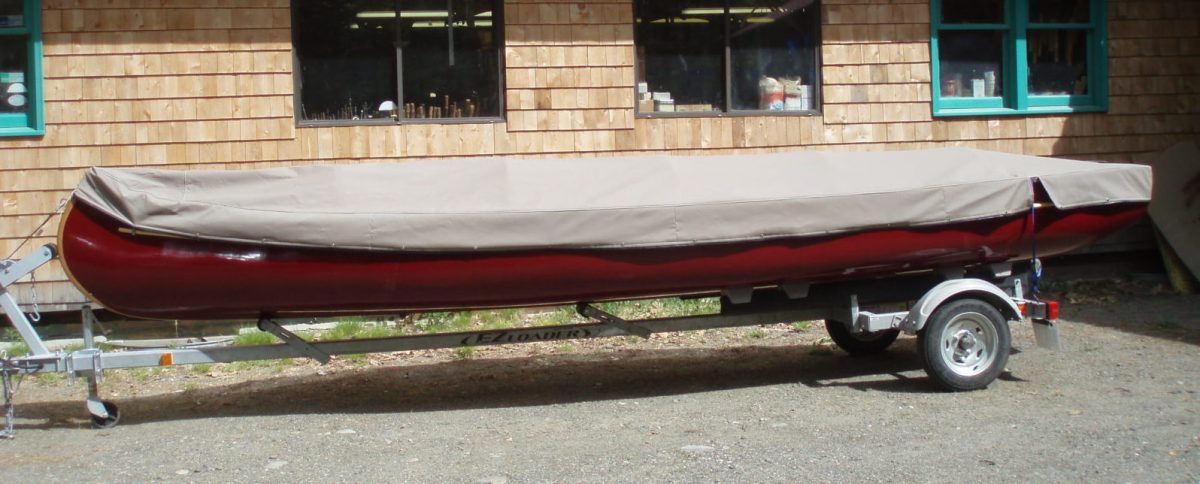 A voyager on a trailer with a canvas cover.